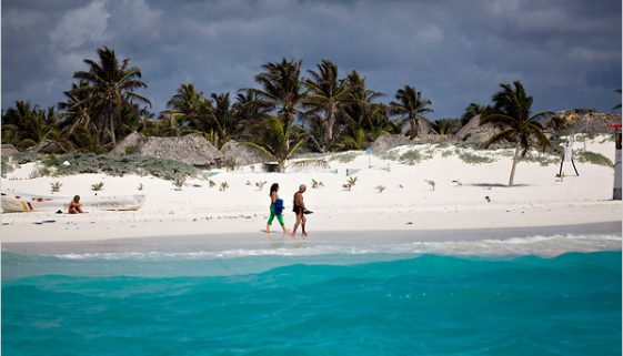 Tourists walk along the beach in front of Zazilkin, a hotel with rustic cabanas in Tulum, on the Yucatán Peninsula. Photo by Michael Nagle.